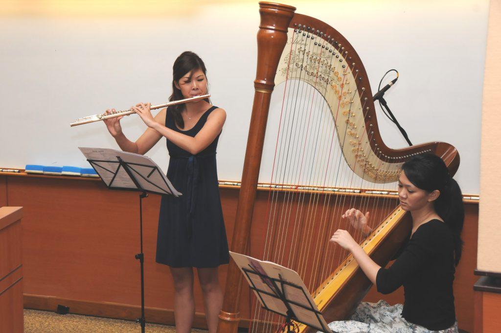 "Musical interlude: (From left) Kelly LOH (flute), Mifiona QUAH (harp)  <i class=""fas fa-video""></i>"